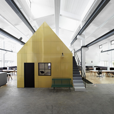 Dossier de presse | 902-02 - Communiqué de presse | A' Design Awards 2014 Les Gagnants Annoncés - A' Design Award and Competition - Concours -  Halle A by Designliga <br>Workspace design by Designliga<br><br>PROJECT DESCRIPTION:<br>//Customer info: Halle A is the studio of the Designliga design bureau and Form & Code, its strategic partner in Web and application development.// //Task: Design and execution interior architecture (LP 1-8), design furnishings.// //Solution: Until its conversion, 10.4-metre-high hall was a metal-working shop for the Munich utilities company Stadtwerke München. The initial intention of preserving the character of the hall was carried out, and a studio was created which builds on the industrial atmosphere of the space and continues its external features throughout its interior. The colour palette is based on the materials and textures prevalent in the complex, whose brick buildings primarily house skilled trades. The structure of the hall interior is determined by two ridge-roof buildings containing two floors of individual offices. Together with the old foreman's office, they form an ensemble which produces the effect of a roofed village square in the intervening space. Despite the size of this space, it is divided into distinct zones and functional areas which creates a feeling of intimacy. The upper area of the space is taken up by the top floors of the buildings and the two conference and meeting-rooms in the old foreman's office. The kitchen is designed as a private room for staff, while the library is where visitors are received and spontaneous meetings are held. The cabinets lining the walls each end in a counter-top that designates the start of the work area. These cabinets combine a variety of functions; they are used for storage and filing, as well as serving as standing workplaces and reception counters. Halle A is a studio, workplace and living space for the people that work here and for our visitors.//   - Crédit photo : Designliga; photographer: Pascal Gambarte, 2013.<br>