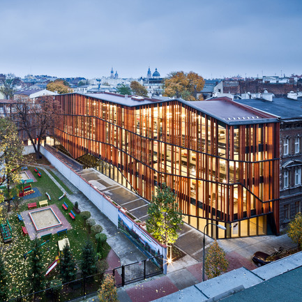 "Dossier de presse | 902-02 - Communiqué de presse | A' Design Awards 2014 Les Gagnants Annoncés - A' Design Award and Competition - Concours -  Malopolska Garden of Arts (MGA) <br>Performing arts centre & mediatheque by Ingarden & Ewý Architects<br><br>PROJECT DESCRIPTION:<br>The building of MGA introduced new spatial order to the old backyards and ruined buildings in Rajska and Szujskiego streets in Krakow. The starting point was a multifunctional hall, which was entered into the outline of the old, 19th-century horse-riding arena, used in the last years of its history as workshops and storage space for the Juliusz Słowacki Theatre in Kraków. The Małopolska Garden of Arts is a cross between two institutions: the Juliusz Słowacki Theatre and the Malopolska Voivodeship Library. The wing on Szujskiego street holds a modern art and media library, with multimedia books and music, while the section standing on Rajska street has been developed by the theatre, and is equipped with a multifunctional events hall. The new hall – operating, as a studio theatre, conference room, concert hall, and venue for banquets and exhibitions – holds retractable stages for 300 people. State-of-the-art stage technology is present overhead: fixed on hoists and cranes to the steel ceiling girders. This allows dramas and concerts to be performed, and exhibitions, film screenings, symposiums, conferences, art auctions, fashion shows, and many more events to be held. Altogether, the space of about 4300 sq.m houses a theatre together with a cosy cinema with 98 seats, a café, and premises for the organisation of educational, art-related activities. Honing the form, the architects focused on interaction with the future recipients, which is why the entire spatial form of the symbolic, openwork roofing raised over the garden from the side of Rajska Street – though not functioning as an actual roof – is there to transport the gateway to the stage out onto the street. In this way, the building delicately nudges passers-by with the skilful manipulation of the form, already at first glance giving the onlooker the impression of going beyond the borders of a garden, where culture is grown in evenly planted rows. Further proof of the sophisticated play with the space is the garden itself. Imitating flower beds, the equal bands with low greens are a metaphor of a garden: as much as the architects could afford here. A notable fact is that historically ""ulica Rajska"" – literally ""Paradise Street"" – led to the Garden of Paradise, which was later replaced by the developments of the Tobacco Works. The final impact is the result of the designers' sensitivity to signals coming from the environment. For example, the opening in the perforated roof of the garden was formed, especially for the maple tree that grows there. In this place, the cultural life of the Kraków's young artistic set will blossom under a shared roof. Modern ballet, contemporary theatre forms, audio and video arts, concerts, and all and any other artistic pursuits will find their home here.  - Crédit photo : Marcin Czechowicz / MURATOR ©, 201"