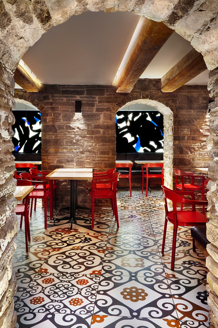Press kit | 1048-09 - Press release | Spanish-inspired tapas restaurant Barsa Taberna captures the energy of the running of the bulls - +tongtong - Commercial Interior Design - View of the old stone archways in the dining room area with in the background the backlit mural - art directed by +tongtong and art:  by Pascal Paquette.<br> - Photo credit: Lisa Petrole Photography<br>