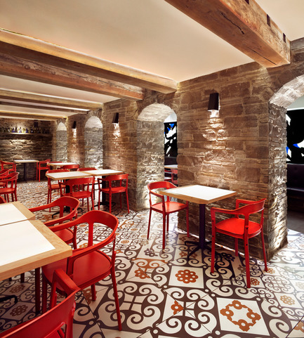 Press kit | 1048-09 - Press release | Spanish-inspired tapas restaurant Barsa Taberna captures the energy of the running of the bulls - +tongtong - Commercial Interior Design - Old stone archways differentiate the grotto-style dining area, a very tight, dark and windowless space with low ceilings and wooden beams. The tiles running throughout the space is purposefully laid to draw attention to the nonlinear nature of the space. The tile pattern itself is a modern take on traditional patterns from the art nouveau and gothic periods.<br> - Photo credit: Lisa Petrole Photography<br>