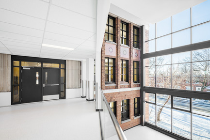 Press kit | 752-03 - Press release | Une jeune funambule de bronze... accueille les écoliers de Parc-Extension - NFOE et associés architectes - Institutional Architecture - Full-height glazed atrium highlights one of the older brick facades - Photo credit: Charles Lanteigne