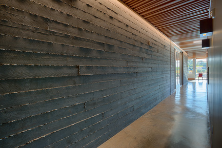 Press kit | 2039-01 - Press release | Titus Vineyards - MH Architects - Industrial Architecture -      The concrete board-form walls that from the exterior façade continue at the interior and provide a textured surface for a recessed LED light above.  Matching interior and exterior finish materials allowed for a blending between the two spaces.   - Photo credit:   Technical Imagery Studios
