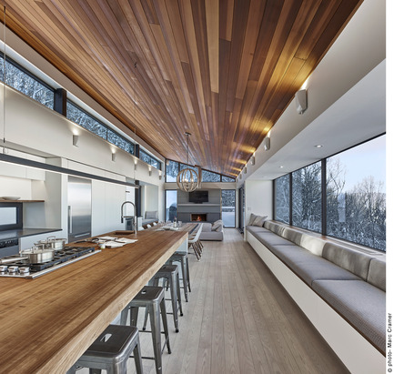 Press kit | 2054-01 - Press release | Laurentian Ski Chalet - RobitailleCurtis - Residential Architecture - View of American cherry island counter surface and 27' bay window with upholstered windowseat - Photo credit: Marc Cramer