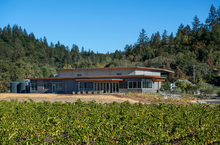 Press kit | 2039-01 - Press release | Titus Vineyards - MH Architects - Industrial Architecture -    The west façade of Titus Winery is characterized by the covered Hospitality area overlooking surrounding vineyards.  Exterior materials include cedar soffits, concrete board-form tilt-up walls, gunmetal blue panels above windows, and anodized aluminum window frames.     - Photo credit: Technical Imagery Studios