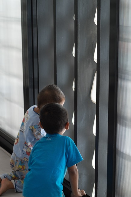 Dossier de presse | 2560-01 - Communiqué de presse | 'Microlibrary Bima': 2000-Ice-Cream-Bucket-Project - SHAU - Institutional Architecture - Children looking out through the ice cream bucket facade of Microlibrary Bima - Crédit photo : Sanrok studio/ SHAU