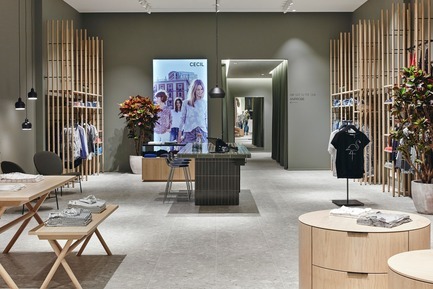 Press kit | 2506-03 - Press release | How to Dress - AGROB BUCHTAL - Commercial Interior Design - Harmonious, inviting, fresh: the Cecil Retail Laboratory in Oberhausen features natural oak, a warm shade of green, real plants and up-to-date advertising images. - Photo credit: Agrob Buchtal GmbH / Mikko Ryhänen