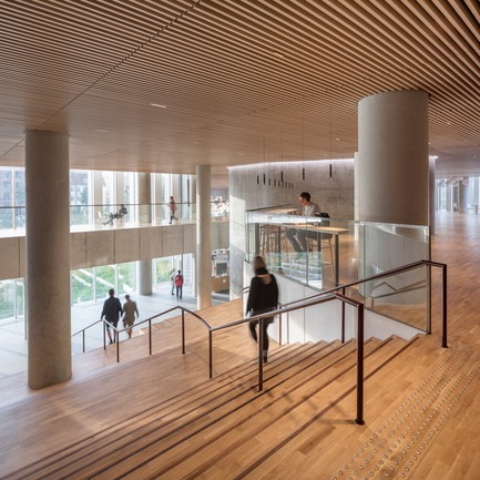 Press kit | 1379-01 - Press release | The Maersk Tower - C.F. Møller Architects - Institutional Architecture - The entrance staircase stands like a piece of furniture in the room, with its warm wooden surface inviting you to pause on the elevated seating steps. - Photo credit:   Adam Mørk