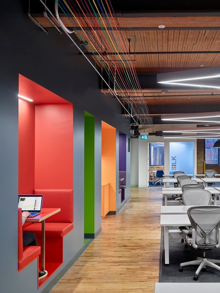 Dossier de presse | 1513-01 - Communiqué de presse | Slack Toronto Office - Dubbeldam Architecture + Design - Design d'intérieur commercial -  Breakout spaces in vivid colours are carved out of the central volume, for impromptu meetings and collaboration. These provide a contrast to the netural palette of the workstations, with automated sit-to-stand desks and chairs by Herman Miller.<br>  - Crédit photo : Shai Gil