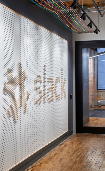 Press kit | 1513-01 - Press release | Slack Toronto Office - Dubbeldam Architecture + Design - Commercial Interior Design -  Opposite the elevator, a pegboard fabricated by local Atelier Kozak greets guests with company slogans and logos. It can be reorganized by employees, inviting playfulness and creativity.<br>  - Photo credit: Shai Gil