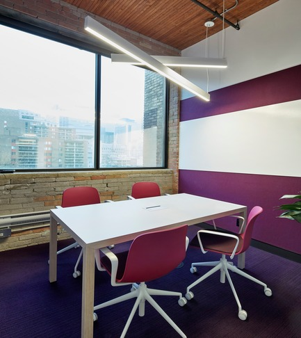 Press kit | 1513-01 - Press release | Slack Toronto Office - Dubbeldam Architecture + Design - Commercial Interior Design -  Meeting rooms are each coordinated around a different, bold colour. This room features a dark magenta carried through the Stylex chairs,Interface carpet, and Designtex acoustic wallcovering, which is offset by the whiteboard, Actiu meeting table edged in birch, and angled white light fixtures by Lumenwerx.<br>  - Photo credit: Shai Gil