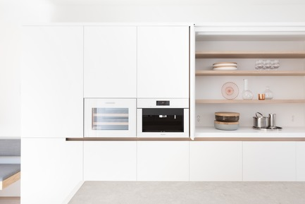 Press kit | 1876-01 - Press release | UnlikelyVancouver Lot Spurs Innovative House Design by Falken Reynolds Interiors - Falken Reynolds Interiors - Residential Interior Design - White lacquer millwork with integrated wine & coffee appliances in white glass to match; open shelving behind doors that tuck away with Corian Solid Surface counter and splash, Bocci 22 outlets and lighting switch - Photo credit: Ema Peter