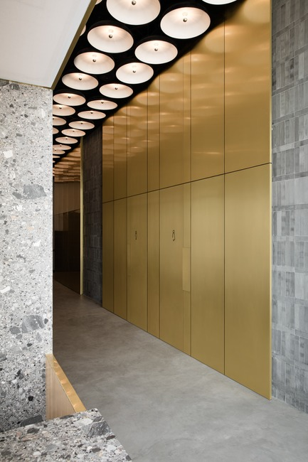 Dossier de presse | 3809-01 - Communiqué de presse | Warehouse GYM D3 - VSHD Design - Design d'intérieur commercial - The main corridor cladded in gold copper alloy leading to the male and female changing rooms with concealed doors of the same material. - Crédit photo : Nik and Tam