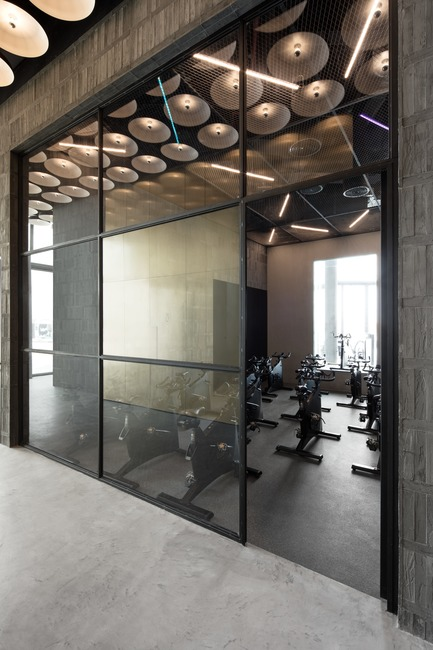 Press kit | 3809-01 - Press release | Warehouse GYM D3 - VSHD Design - Commercial Interior Design - View into the cycling studio with ceiling lights creating a dynamic element throughout the gym. - Photo credit: Nik and Tam