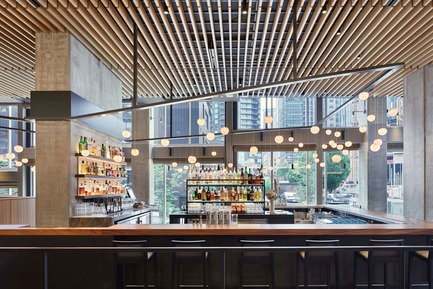 Dossier de presse | 2886-02 - Communiqué de presse | Wild Ginger Denny Triangle - SkB Architects - Commercial Interior Design - View through the bar featuring the cantilevered custom light fixture also designed by the architects - Crédit photo : Ben Benschneider