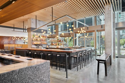 Dossier de presse | 2886-02 - Communiqué de presse | Wild Ginger Denny Triangle - SkB Architects - Commercial Interior Design -  Central bar area and dining with custom light fixture feature Bocci globes above  - Crédit photo : Ben Benschneider