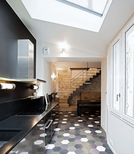 Dossier de presse | 3894-01 - Communiqué de presse | Une maison de ville unifamiliale à Paris - Alia Bengana + Capucine de Cointet architectes - Architecture résidentielle - Kitchen open to the entrance and dining room, cement tile floor, steel and stainless steel door kitchen and black granite worktop<br> - Crédit photo : David Cousin-Marsy