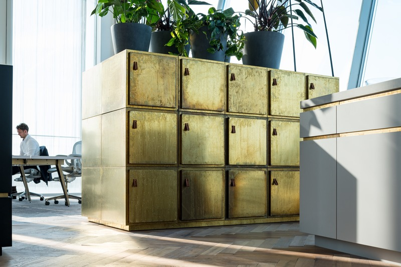 Dossier de presse | 3644-02 - Communiqué de presse | One of the Best Offices in the World - Firm architects - Design d'intérieur commercial - The custom designed lockers are covered in acid aged brass paneling to add richness the central informal areas.   - Crédit photo : Studio de Nooyer
