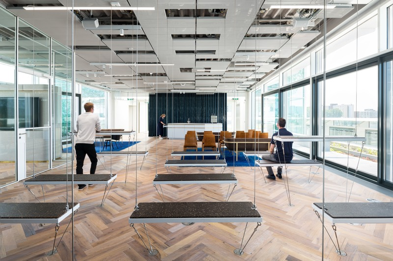 "Dossier de presse | 3644-02 - Communiqué de presse | One of the Best Offices in the World - Firm architects - Design d'intérieur commercial - <p class="""">The flexbenches on the 5th floor in the Skyroom. With the push of a button they descent from the ceiling to form extra seating space and tables. The skyroom is surrounded by the boardroom and the flexible roof gardens.</p> - Crédit photo : Studio de Nooyer"