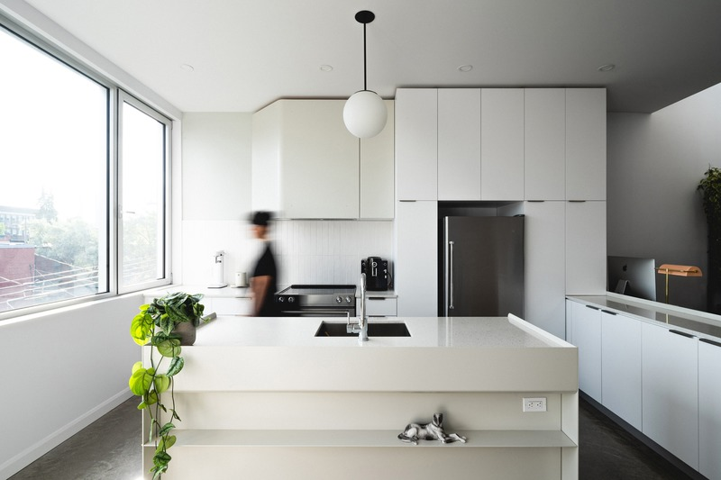 Press kit | 1142-07 - Press release | Off Plaza: L. McComber meets la Maison du Rotin - L. McComber – architecture vivante - Residential Architecture - The compact but sunny kitchen, open to the city and living areas. - Photo credit: Raphaël Thibodeau