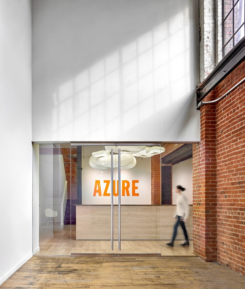 Press kit | 1513-05 - Press release | Azure Publishing Office - Dubbeldam Architecture + Design - Commercial Interior Design - The entry is demarcated by its distinctive logo, rendered in a bold orange supergraphic, visible through the reception glass on axis at the end of a long corridor leading to the office. - Photo credit: Scott Norsworthy