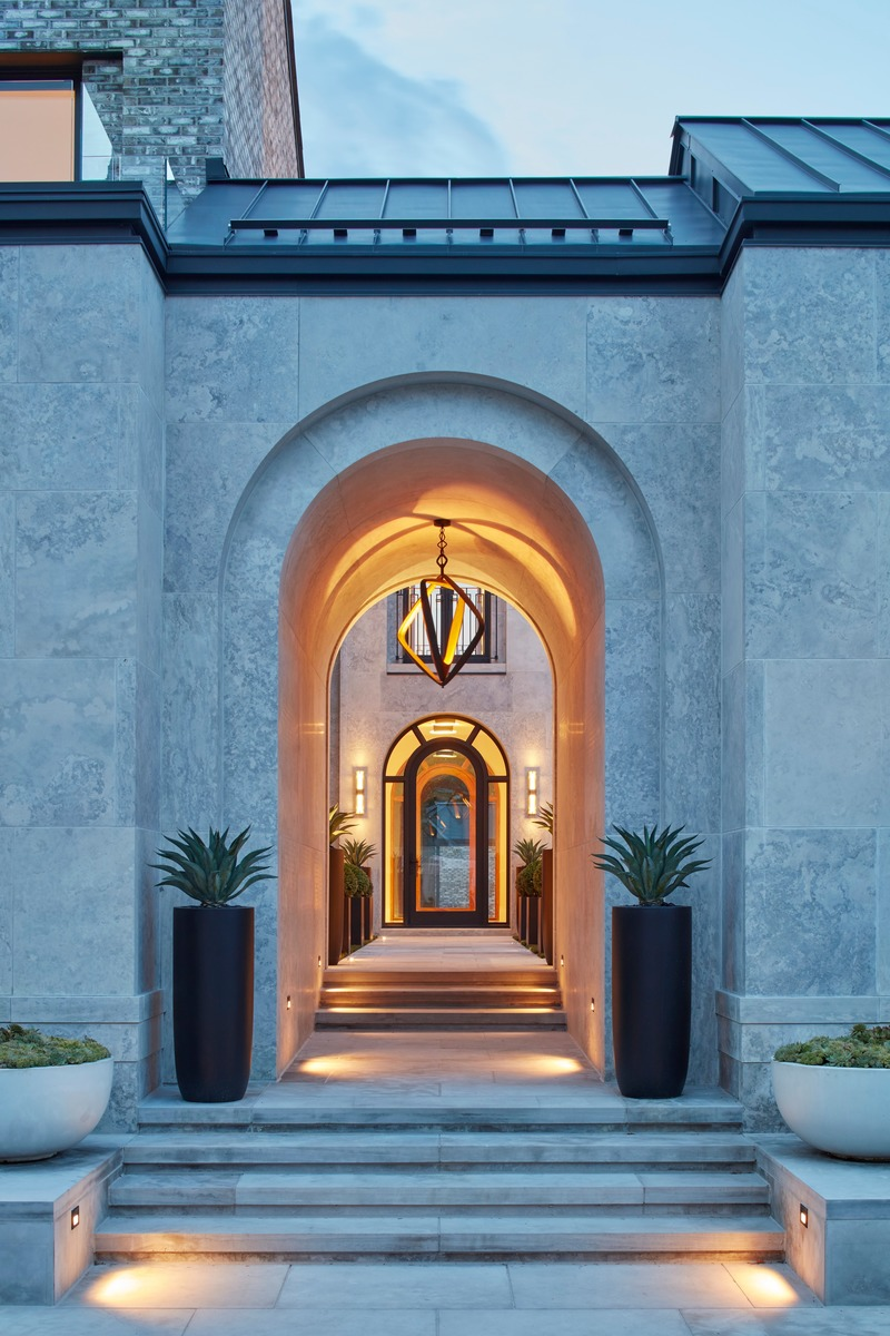 Press kit | 2185-07 - Press release | Villa Cortile - Audax - Residential Architecture - The front entryway features a tall archway with a Porta Romana chandelier as the centerpiece. The path following leads through the courtyard to arrive at the front door. The archway motif, used throughout the home, was inspired by the streets of urban Italy that feature unique entryways to courtyards and piazzas. - Photo credit: Shai Gil
