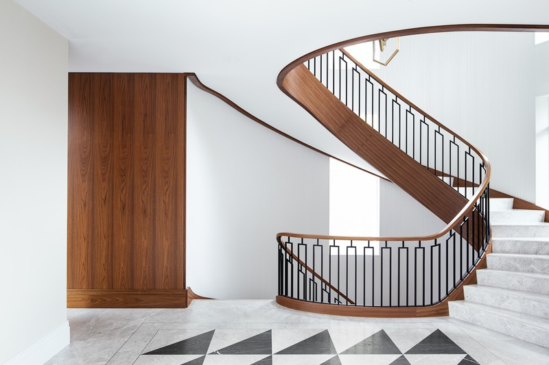 Press kit | 2185-07 - Press release | Villa Cortile - Audax - Residential Architecture - The grand staircase, finished with a walnut handrail and accents, marble steps with brass detailing, and fluted plaster along the adjoining wall. - Photo credit: Erik Rotter